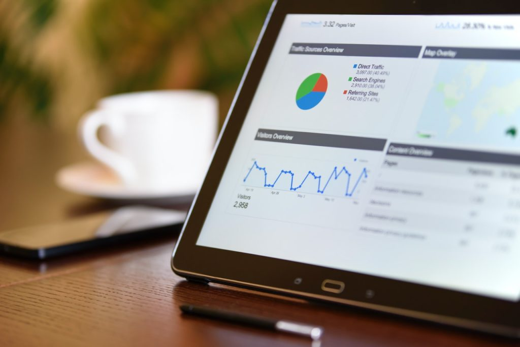 Web analytics on a tablet sitting on a table next to a coffee cup, a pen and a phone