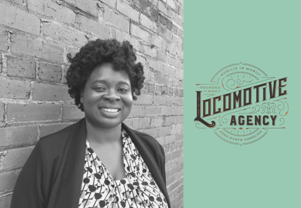 Amanda Jordan smiling against a brick wall, the LOCOMOTIVE Agency beside her